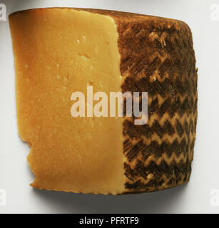 Dark yellow Cabrales cheese, a Spanish cheese made from cow, sheep, and goat's milk, wrapped in chestnut leaves and aged in a humid cave. Dark brown rind with yellow zigzag stripes - Stock Photo