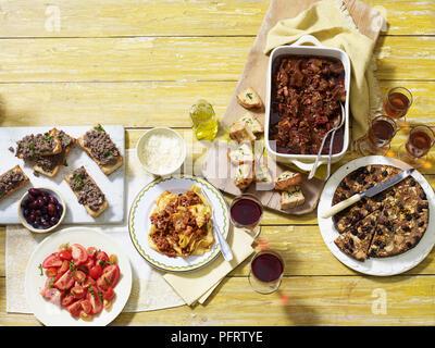 Tuscan autumn supper, including crostini di fegatini (chicken liver), pappardelle al ragu, spezzatino di manzo (beef stew), castagnaccio chestnut cake - Stock Photo