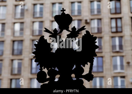 'Two empires': silhouette of the coat of arms of Russian Empire with a wall of typical high-rise Soviet era building in the background; Saint Petersbu - Stock Photo