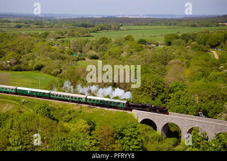 An old steam train on a bridge in countryside, England, UK - Stock Photo