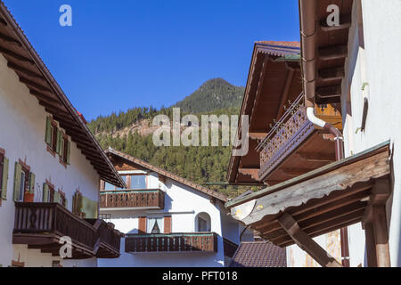 Garmisch-Partenkirchen, Germany - April 7, 2018 - street view of of traditional austrian style houses with mountains in the background - Stock Photo