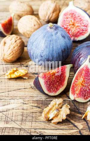 Fresh figs whole and cut with walnut kernels on a wooden old background - Stock Photo