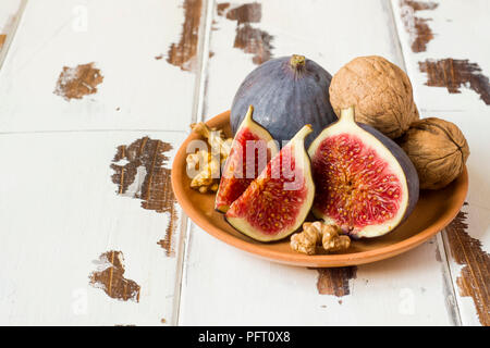 Fig walnuts cinnamon anise on a plate of old wooden background - Stock Photo