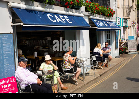 UK, Cornwall, Padstow, The Strand, visitors sat in sunshine outside waterfront Fish and Chip shop - Stock Photo