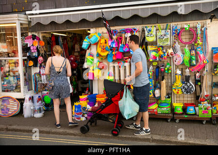 UK, Cornwall, Padstow, Market Place, young family outside beach supplies and toy shop - Stock Photo