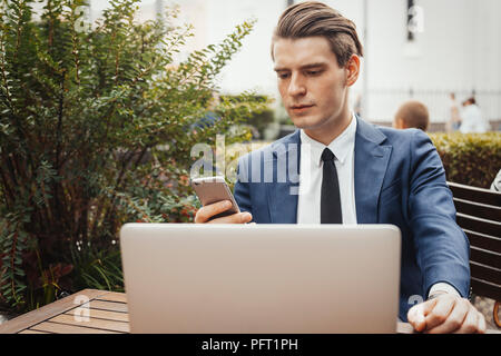 Business man holding mobile phone in hand and sitting next to laptop. Front view - Stock Photo