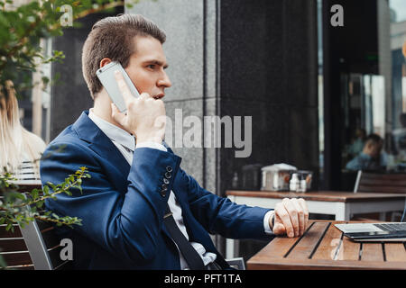 Young attractive brunette businessman talking by mobile phone in cafe. - Stock Photo