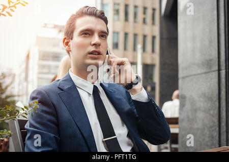 Young brunette businessman talking by mobile phone and looking straight. - Stock Photo