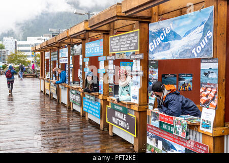 Tour operators hopefully touting for business on a rather wet day in the harbour at Juneau the capital city of Alaska, USA - Stock Photo