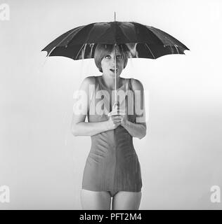 1960s woman. A young woman in a bathing suit is standing under an umbrella.  Sweden 1960s ref DO42-3 - Stock Photo