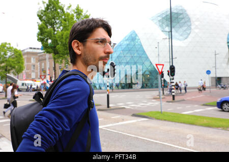 Young man with backpack waiting taxi or bus in Mathildelaan main street in Eindhoven, Netherlands - Stock Photo