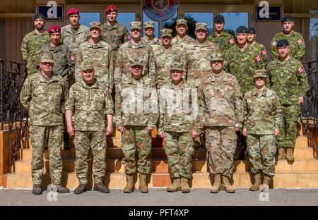 Yavoriv, Ukraine – Canadian, Lithuanian, Polish, Ukrainian, and U.S. Soldiers pose for a photo during a visit from Maj. Gen. Raymond Shields to the Yavoriv Combat Training Center here May 25. During his visit Shields met with JMTG-U leaders and awarded challenge coins to U.S. service members to recognize them for all of their hard work. - Stock Photo