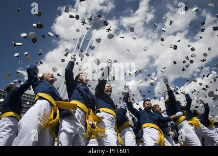 The U.S. Air Force Thunderbirds perform a fly-over as graduates from the Air Force Academy toss their hats in the air at the conclusion of their commencement ceremony in Colorado Springs, Colorado, May 23, 2018. - Stock Photo