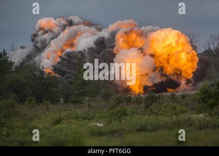 A mine clearing line charge (MICLIC) explodes as U.S. Marines with Mobility and Counter-Mobility Platoon, 2nd Assault Amphibian Battalion, 2nd Marine Division engage training targets during a deployment for training (DFT) exercise at Fort Stewart, Ga., May 29, 2018. When employed, the MICLIC can clear and destroy improvised explosive devices, greatly enhancing troop mobility on the battlefield. The DFT helps maintain proficiency in landing the surface assault element during amphibious operations to inland objectives with conduction mechanized operations and related combat support in operations - Stock Photo