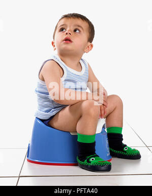 Boy wearing vest and slippers, sitting on potty, 15 months - Stock Photo