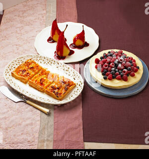 Dessert collection, apricot and almond galette, poached pears with blackberry sauce, lemon cheesecake topped with fresh berries - Stock Photo