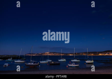 Small boats at night in Rhos-on-Sea harbour on the North Wales coast - Stock Photo