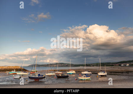 Small boats at low tide in Rhos-on-Sea harbour on the North Wales coast - Stock Photo