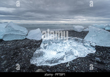 Icebergs washed onto a black sand beach at Jokulsarlon Glacier in Iceland on a beach known as Diamond Beach. - Stock Photo