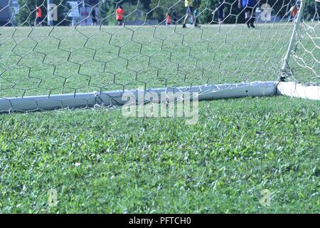 Australia - May 20, 2018: portrait orientation closeup of soccer goal and net resting on grass with players running in background. - Stock Photo