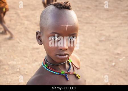 Beautiful young african boy with traditional necklaces mysterious cross sign on forehead from Hamar tribe looking curiously with striking shiny eyes - Stock Photo