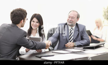 handshake between colleagues in the workplace in the office - Stock Photo