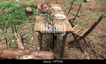 tourists take pictures of the table set for a romantic picnic in the woods - Stock Photo