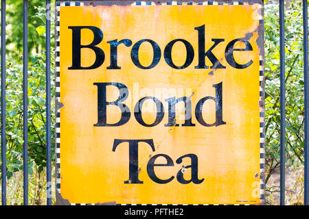 Close up of vintage enamel advertising sign, signage fixed to railings outside UK Severn Valley Railway station 'Brooke Bond Tea'. Antique artefact. - Stock Photo