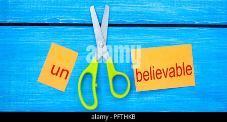 scissors cut the word unbelievable. concept believable. cuts the word 'un. 'I can, goal achievement, potential, overcoming - Stock Photo
