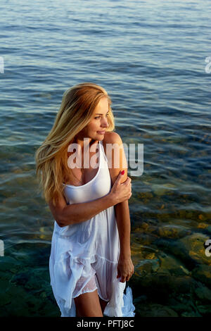 beautiful-blonde-girl-standing-knee-deep-in-sea-water-wearing-a-white-tunic-pftj8c Getting a Bride Web based