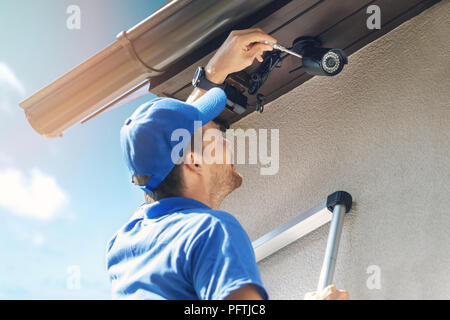 man install outdoor surveillance ip camera for home security - Stock Photo