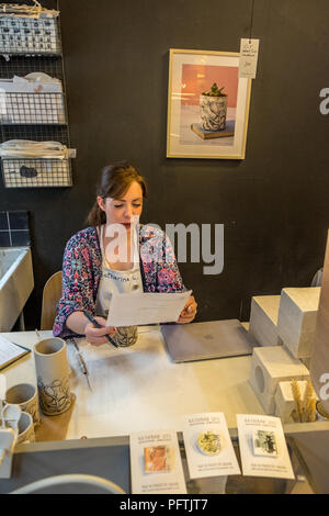 A young lady working in her workshop making ceramic jugs - Stock Photo
