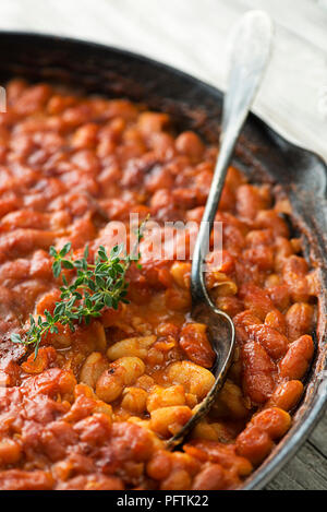 Baked beans stew with tomato sauce and meat with herbs close up - Stock Photo