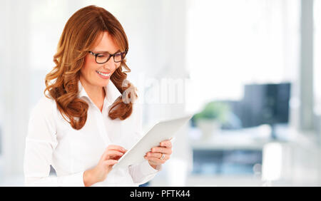 Portrait of a confident financial assistant using her digital tablet in the office. - Stock Photo