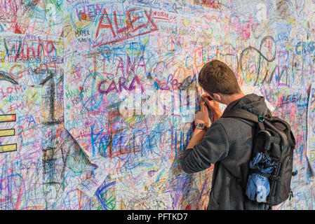 A young man writing on the Peace Wall  by Yoko Ono to 'Add colour where the world needs peace' at  the 'Double Fantasy' exhibition in Liverpool - Stock Photo