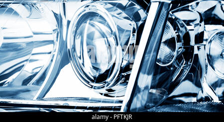Automobile lenticular headlamp in blue tones is shot close-up. - Stock Photo