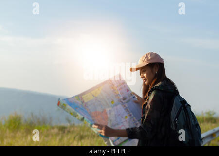 Asian  young women people Hiking with friends backpacks walking together and looking map and taking photo camera by the road and looking happy ,Relax  - Stock Photo