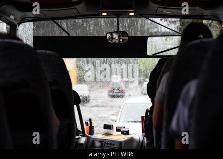 Bad weather outside, view from inside to street through the window, bus with passengers - Stock Photo
