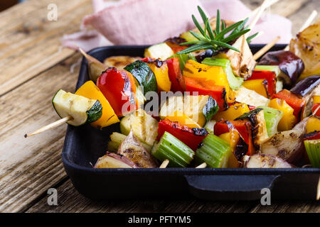 Grilled colorful vegetables skewers on cast iron skillet. Vegan summer meal on rustic wooden table - Stock Photo