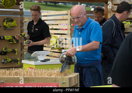 People looking at power tools for sale & man using cordless hedge trimmer - Ryobi trade stand, RHS Chatsworth Flower Show, Derbyshire, England, UK. - Stock Photo