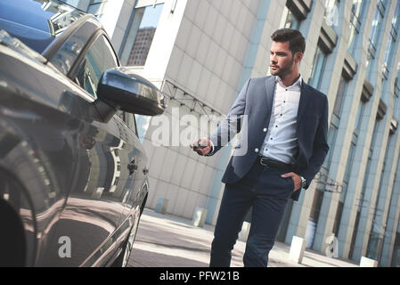 This car is perfect for me. Cheerful mature man in formalwear looking at camera and smiling while standing near his new car - Stock Photo