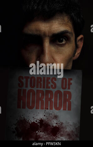 Sinister man looking at camera with a horror book under his face. - Stock Photo