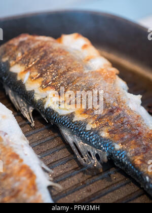 Whole sea bass fish cooking in hot pan close up - Stock Photo