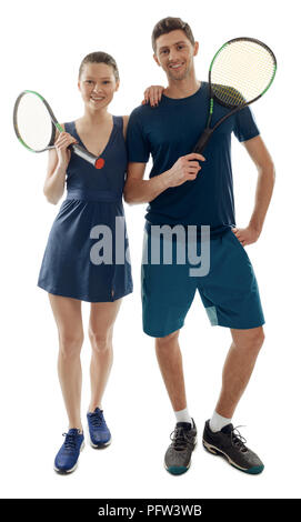 Team players posing on white. Athletic woman and man dressed in uniform and holding rackets. Tennis, hobby and physical activity. - Stock Photo