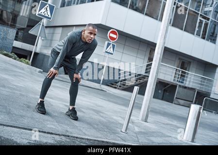 Urban sports. Young man is doing warming up before running in the city on a morning - Stock Photo
