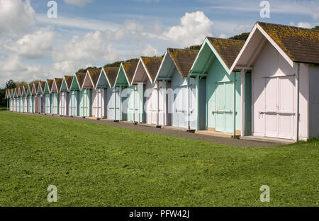 Row of multicoloured beach huts on green behind seafront at Southsea in Portsmouth, Hampshire, England - Stock Photo