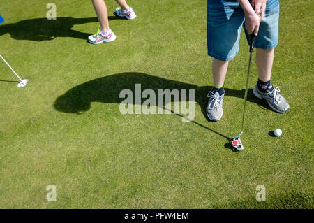 Legs of a young boy teenager preparing to put a golf ball. Cornwall Polzeath - Stock Photo