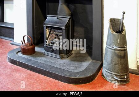 Old fireplace, grate, coal scuttle and enamel kettle in an old house - Stock Photo