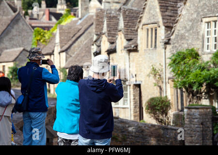 Castle Combe, UK - 9th August 2018: Tourists taking pictures of Castle Combe which is a quintessentially English village often named as the 'prettiest - Stock Photo