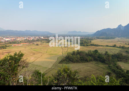 Beautiful view of Vang Vieng town and fields and karst limestone mountains from above near Vang Vieng, Vientiane Province, Laos, on a sunny day. - Stock Photo